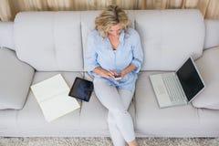 Blont sammanträde på soffan genom att använda hennes smartphone royaltyfri bild