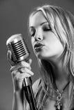 Blont sjunga med tappningmikrofonen Arkivbild