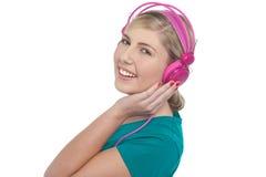 Blont tonårigt lyssna till musik Arkivfoto