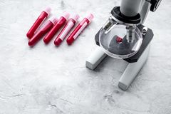 Blood analysis in clinacal lab. Test tubes near microscope on grey background top view copy space. Blood analysis in clinacal lab. Test tubes near microscope on Royalty Free Stock Images
