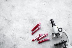 Blood analysis in clinacal lab. Test tubes near microscope on grey background top view copy space. Blood analysis in clinacal lab. Test tubes near microscope on Royalty Free Stock Image