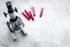 Blood analysis in clinacal lab. Test tubes near microscope on grey background top view copy space. Blood analysis in clinacal lab. Test tubes near microscope on Stock Images