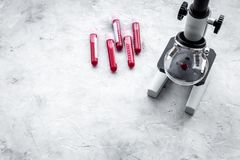 Blood analysis in clinacal lab. Test tubes near microscope on grey background top view copy space. Blood analysis in clinacal lab. Test tubes near microscope on Royalty Free Stock Photography