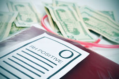 Blood bag and US dollar bills. Closeup of a blood bag with a label with the text O RH positive and a pile of US dollar bills in the background Stock Images
