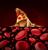 Blood Disease Risk. Medical concept as a group of greasy junk food shaped as the dorsal fin of a dangerous shark swimming in a pool of blood cells as a symbol Royalty Free Stock Photos