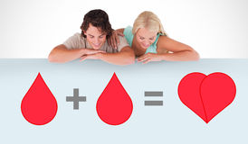 A blood donation sign being looked at. By a couple Stock Photos