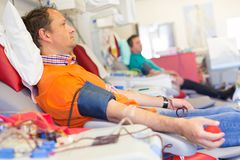 Blood donor at donation. Blood donor at donation with a bouncy ball holding in hand royalty free stock photo