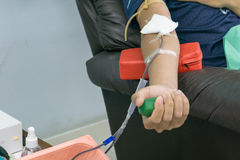 Blood donor at donation with a bouncy ball holding in hand. Stock Photos
