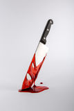 Blood drenched Kitchen knife in pool of blood. Stuck in surface Stock Photography