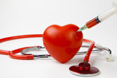 Blood drop. While injecting red heart with syringe on white background stock photo