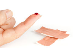 Blood finger and band-aid. Closup of a wounded bleeding finger and an out of focus baind-aid royalty free stock images