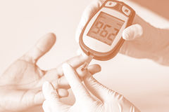 Blood glucose meter, the blood sugar value is measured on a fing Royalty Free Stock Image