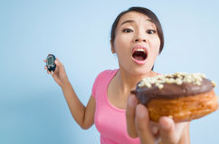Blood glucose meter and a donut. Asian woman hold a blood glucose meter and a donut royalty free stock image