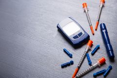 Blood glucose meter, needles and several insulin syringes on a gray wooden table, flat lay with copy space royalty free stock photography
