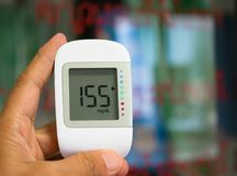 Blood glucose meter. A person holding up a digital blood glucose meter used in home or hospital royalty free stock photos