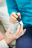 Blood glucose monitoring for old woman Royalty Free Stock Photos