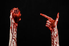 Blood and Halloween theme: terrible bloody hand hold torn bleeding human heart isolated on black background in studio. Blood and Halloween theme: terrible bloody royalty free stock image