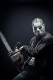 Blood insanity. Guy with bloody chainsaw posing over dark background stock photography