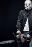 Blood insanity. Guy with chainsaw in mask posing over dark background royalty free stock photos