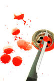 Blood and Knife. A Sharp blood covered knife set on a white background with blood splatters around, over a plug hole in a bath Royalty Free Stock Image