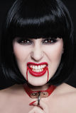 Blood lover. Young beautiful furious brunette with bloody vampire fangs and furious expression royalty free stock photography