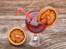Blood orange cocktail with slices of blood orange on wooden table Royalty Free Stock Image