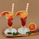Blood Orange Fruit Juice Drink. In glasses on doilies with striped straws on an olive wood board over ridged brown paper background. High in vitamins royalty free stock images