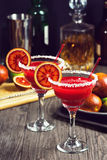 Blood Orange Margaritas with Ingredients. Two blood orange margaritas with salted rims in a vintage-style bar. The ingredients to make the drink are in the Royalty Free Stock Images