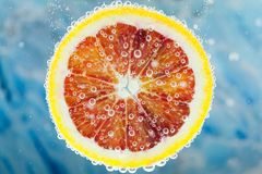 Blood orange slice falling into water. Close-up of slice of citrus blood orange dropped into carbonated water with bubbles on blue background Royalty Free Stock Image