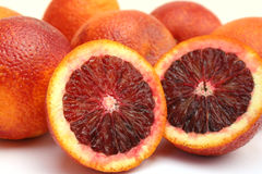 Blood Oranges. Isolated image of two halves of a blood orange resting against several whole blood oranges Royalty Free Stock Photo