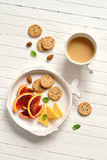 Blood oranges, cheese and crackers in a vintage plate Stock Photo