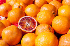 Blood oranges on market stand as background. Blood oranges on market stand with one of them cutted in half royalty free stock images