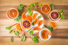 Blood oranges on white plates with salad leaves Stock Image