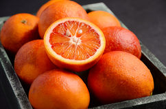 Blood oranges in wooden tray on dark background Royalty Free Stock Photo