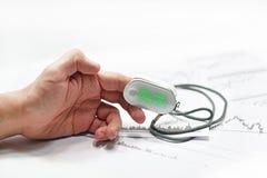 Blood oxygen meter on mans finger. Stock Images