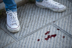 Blood on pavement. Teenage girl shoes, blood on the pavement Stock Image