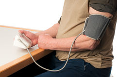 Blood pressure 01. A senior man checking his blood pressure royalty free stock image