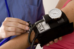 Blood pressure. Doctor or nurse taking a patient's blood pressure Stock Images