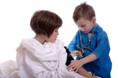 Blood Pressure. Young doctor taking the blood pressure of a patient. Isolated against a white backdrop Royalty Free Stock Image