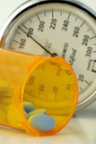 Blood Pressure. Pills in a pill bottle with a blood pressure cuff in the background Royalty Free Stock Photography