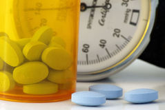 Blood Pressure. Pills in a pill bottle with a blood pressure cuff in the background Stock Image