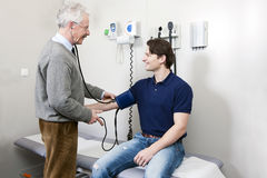 Blood pressure. General practitioner taking the blood pressure off a young patient stock image