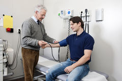 Blood pressure. Friendly doctor taking a blood pressure reading from a young patient during a physical examination Stock Photo