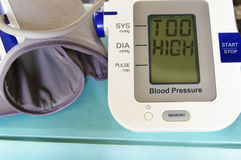 Blood pressure. Arm band with Too High text royalty free stock photos