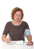 Blood pressure check. Senior woman check her blodd pressure with machine Royalty Free Stock Image