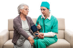 Blood pressure check doctor and old woman at home Royalty Free Stock Images