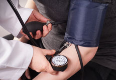 Blood pressure check up. Patient gets Blood pressure check up by the Doctor royalty free stock image