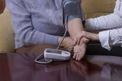 Blood pressure check. Woman checking blood pressure at home Royalty Free Stock Photo