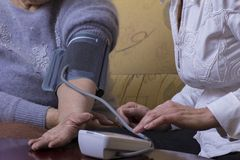 Blood pressure check. Woman checking blood pressure at home Royalty Free Stock Photos