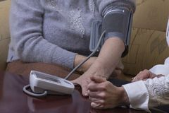 Blood pressure check. Woman checking blood pressure at home Royalty Free Stock Image